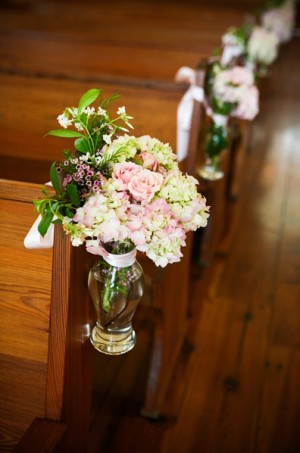 pink-and-green-flowers-in-glass-vase-tied-to-chapel-aisle