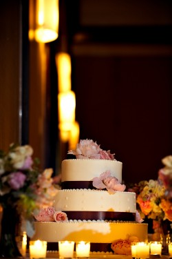 Ivory Wedding Cake with Brown Ribbon and Pink Flowers