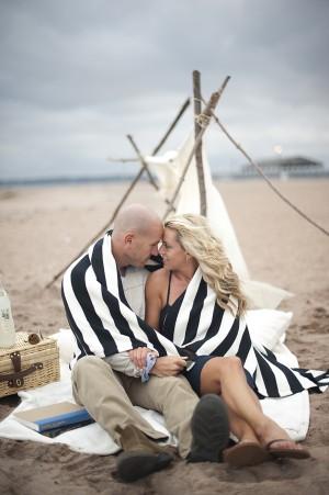 Couple Cuddling on Beach under Blanket