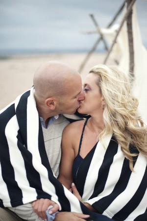 Couple Kissing Under Striped Blanket