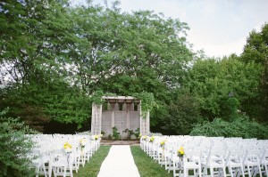 Outdoor Ceremony Site With White Chairs and Yellow Flowers