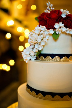 Round Tiered Wedding Cake With Gold Leaf and Red Roses