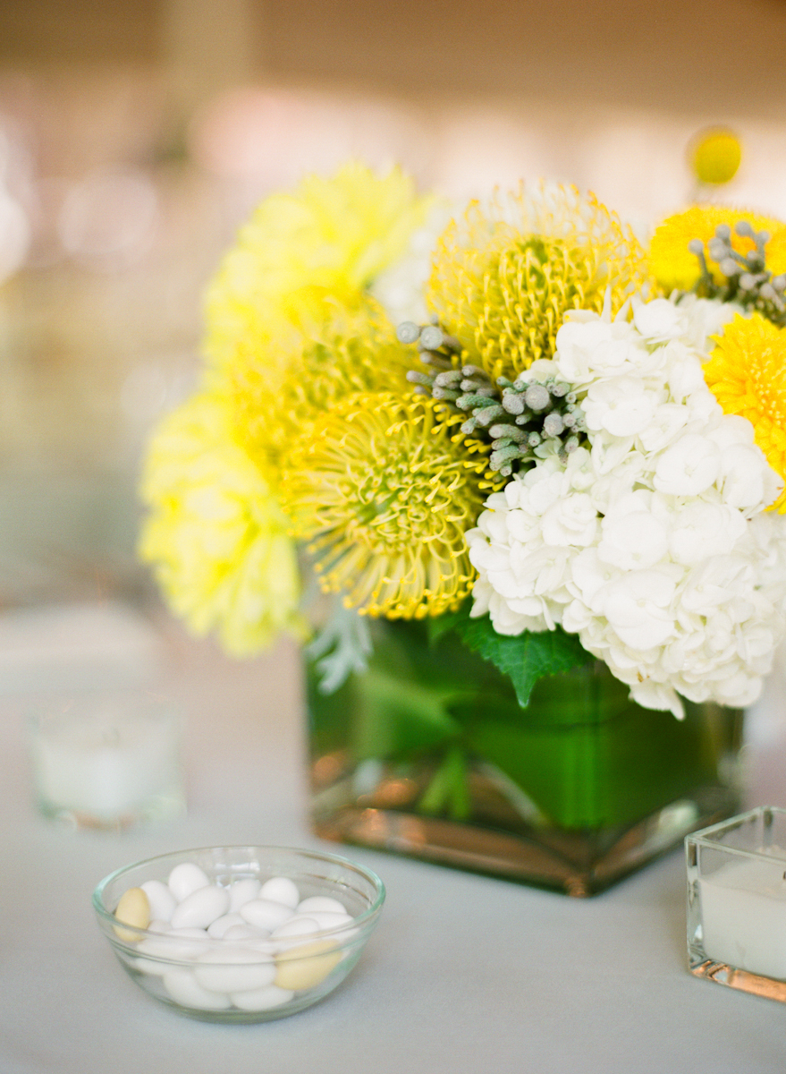 Yellow and white reception centerpiece in square glass