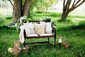 Bench in Grassy Meadow With Pillows Blanket and Candles1