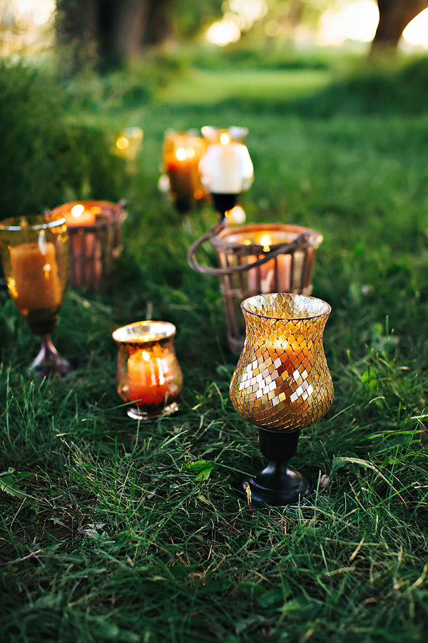 Candles in Amber Colored and Mosaic Vases Sitting on Grass1