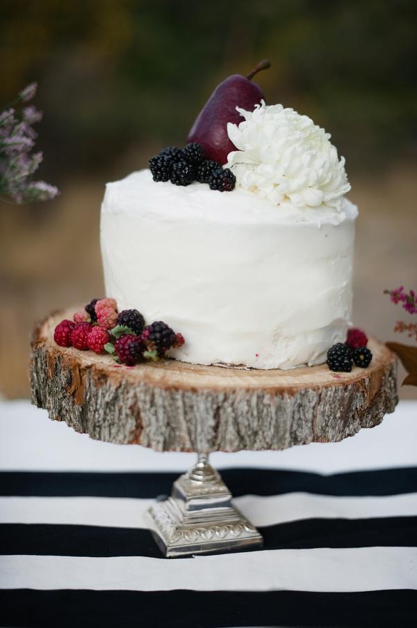 Round White Cake With White Flower And Berry Garnish