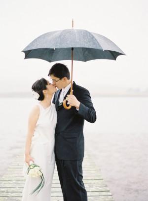 Couple Kissing Beneath Umbrella