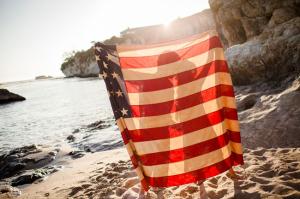 Couple Holding American Flag on Beach
