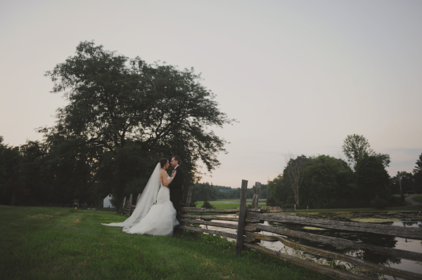 Bride and Groom Leaning on Wood Fence