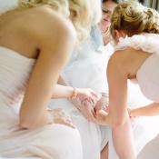 Bridesmaids Helping Bride with Garter