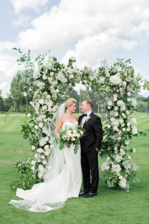 Bride and Groom with Ornate Floral Arch