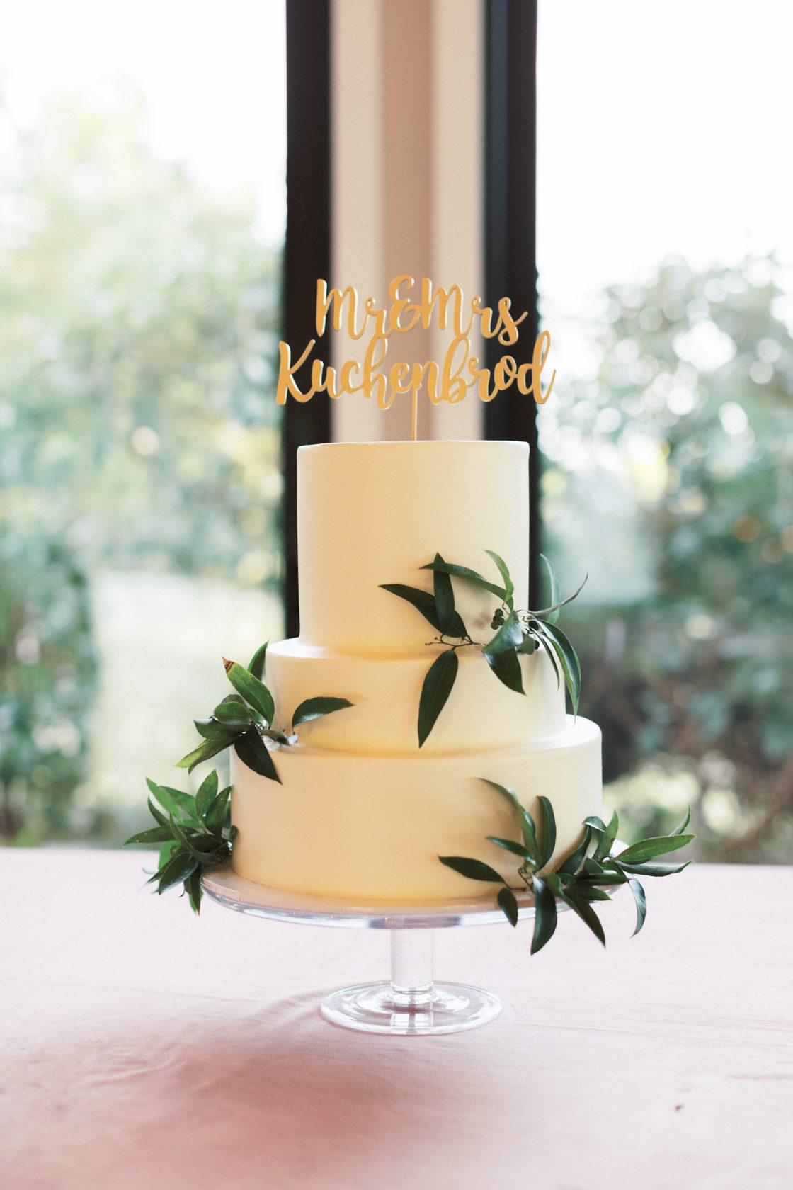 Ivory Three Tiered Wedding Cake with Greenery